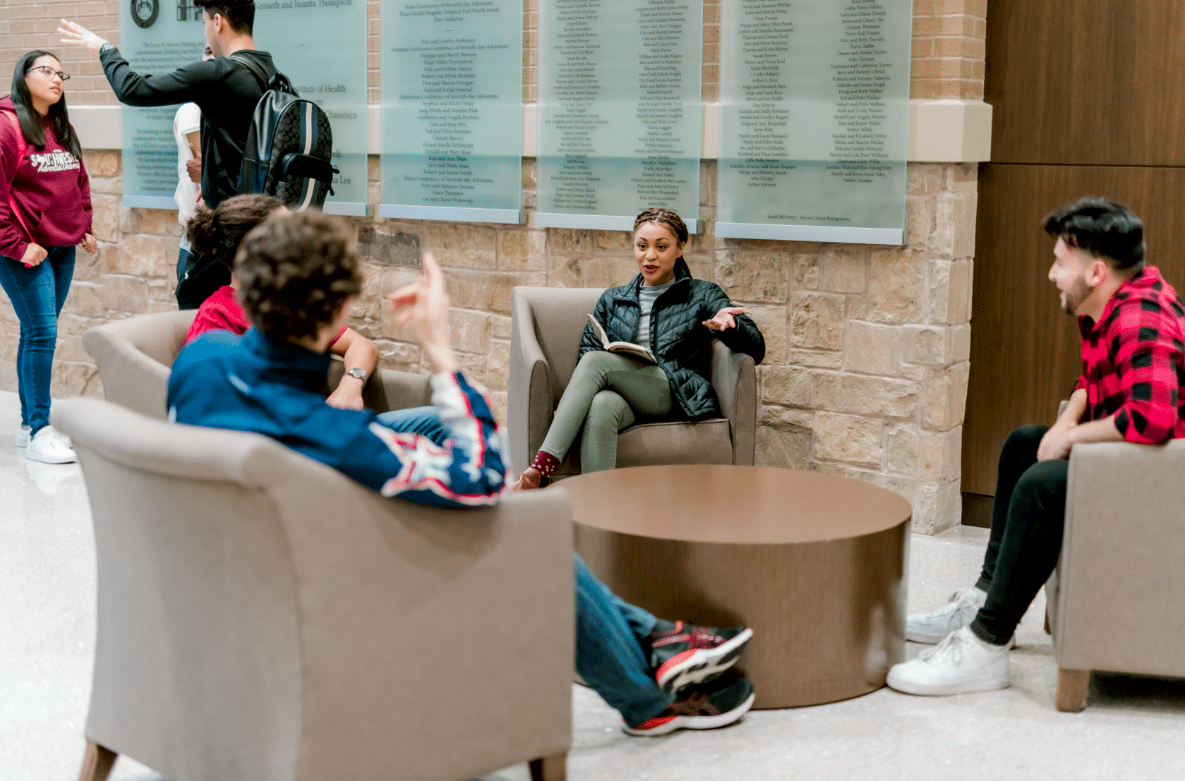Four students sit in singular chairs and talk to each other across a brown coffee table.