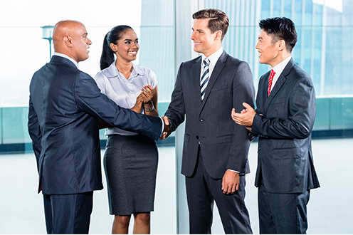 A man steps forward to shake the hand of another man while his two colleagues clap beside him