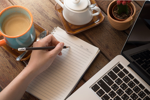 Beside a laptop and cup of coffee, a hand hovers over a notepad as they begin to take notes