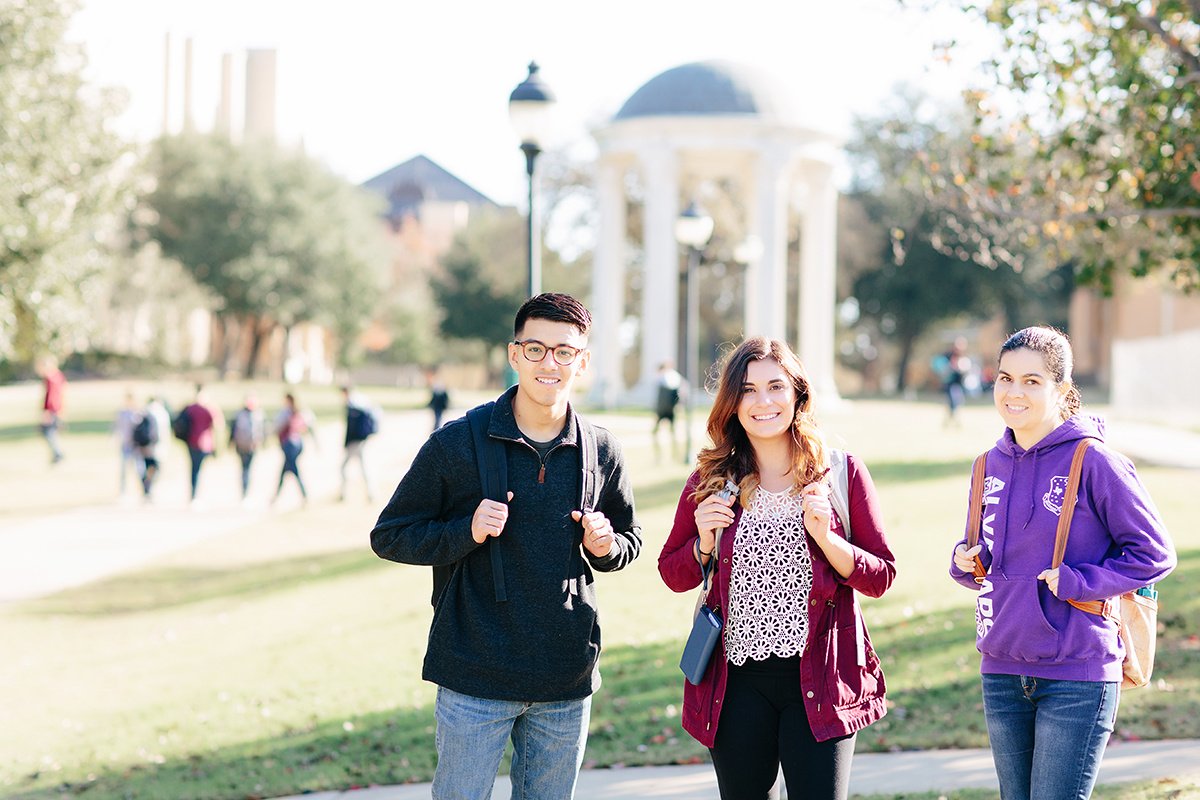 Three students stand togther smiling with their backpacks on infront of the rotunda while other students pass by