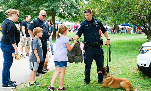 A police officer hands a young girl a a vest to try on as he holds his dog with the other hand