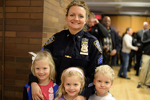 A police officer smiles as three children stand in front of her and smile