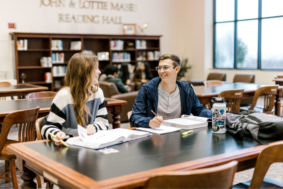 Two students sit together at the library looking at eachother smiling, they have pencilas and studying materials in front of them