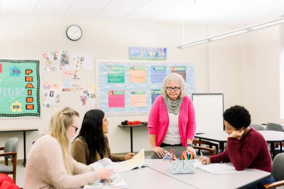 In an educational classroom filled with colorful posters, a professor stands beside a rounded desk, speaking to her students