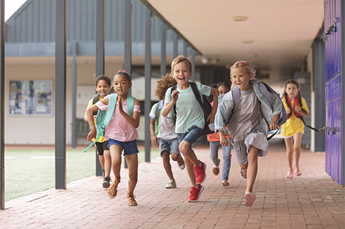 A group of excited young children run with backpacks on