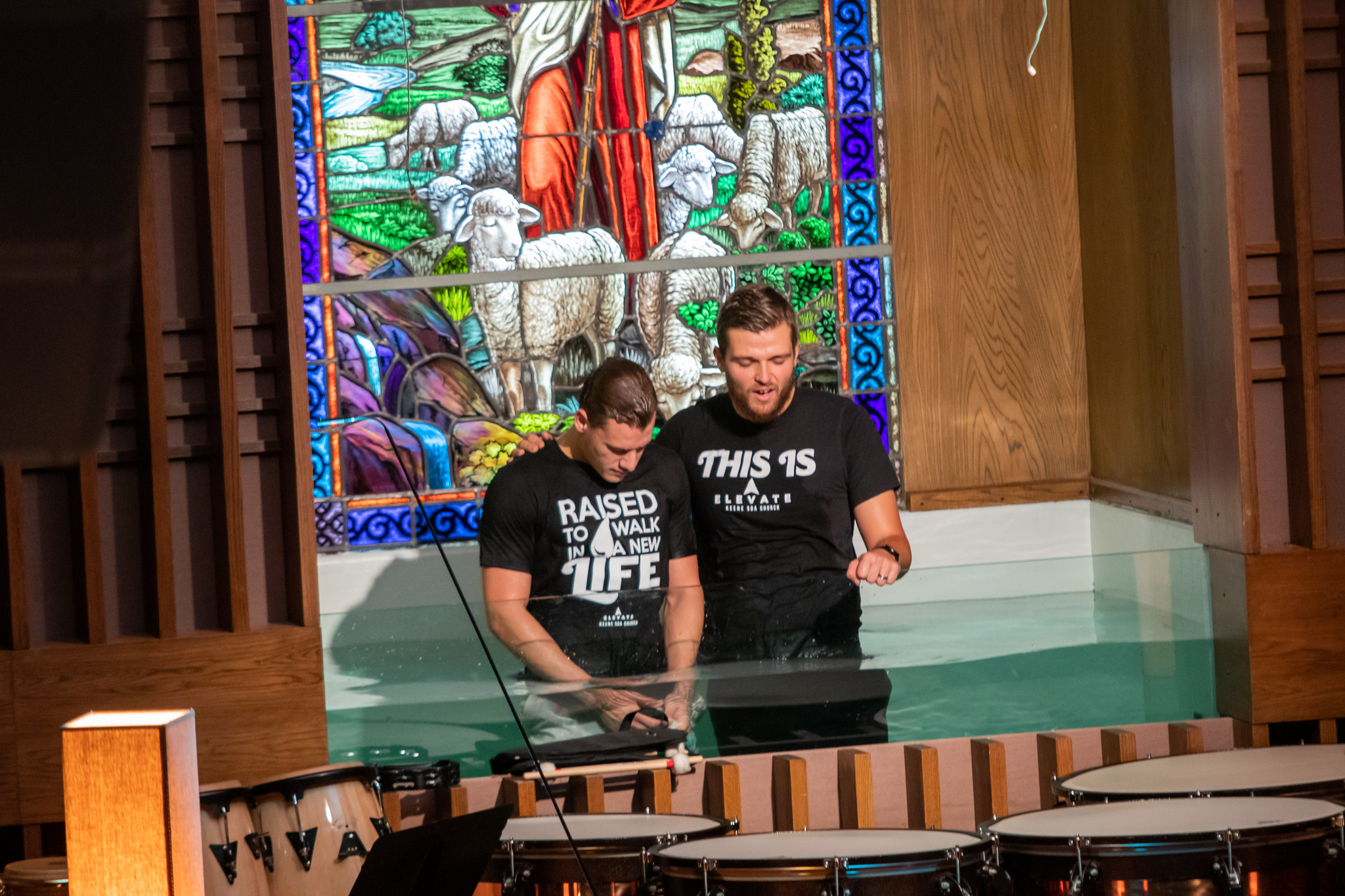 Standing in a baptismal pool, a pastor, dressed in a black t-shirt, prays as he puts his arm over a student, who has just been baptized