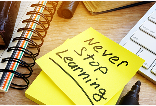 """A yellow sticky note that reads """" Never Stop Learning"""", sits on a desk among a kepboard, books, notepad and more."""
