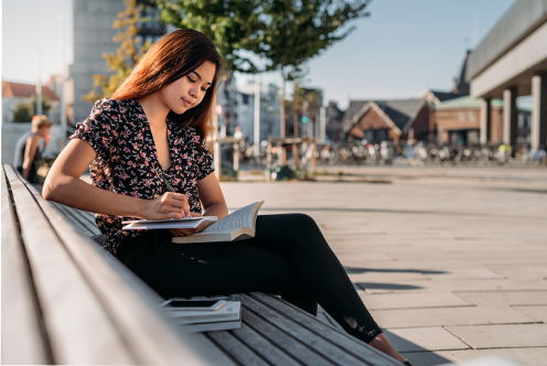 A woman sits outside on a bench and takes notes as she reads