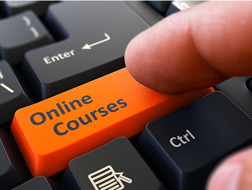 """On a keyboard, a finger presses an orange button that reads, """"Online Courses"""""""