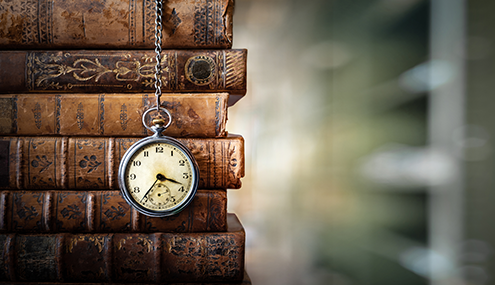 A pocketwatch hangs in front of a stack of older, brown books