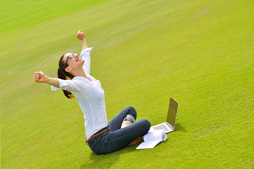 A woman, sitting on the grass with her legs cross, throws her arms up in the air as she sits in front of her laptop and notes