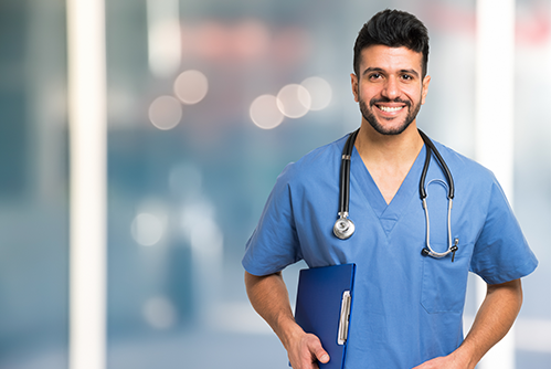 A nurse smiles as he wears blue scrubs along with a stethoscope around his neck smiles
