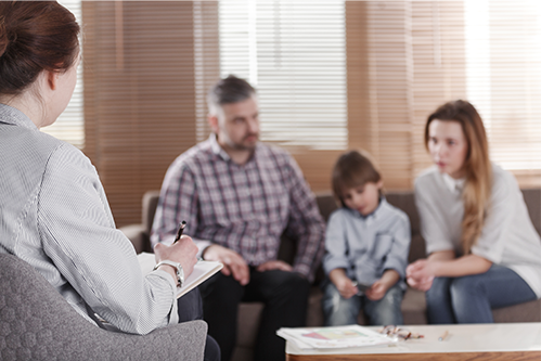 A family of three sit on a couch and they talk to a counselor seated accross from them