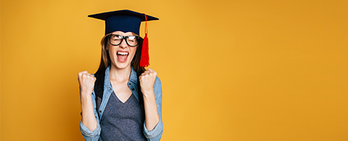 A woman cheers in excitement as she wears a graduation cap with a red tassel