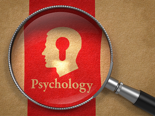 """A magnifying glass focusing in on a writing that says """"Psycology"""" with a picture of a head above it"""