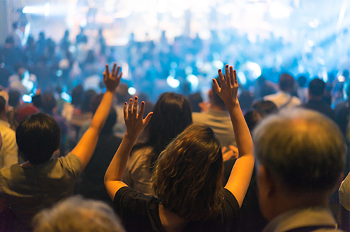 Crowd of people with hands raised in a worship atmosphere, facing a stage from above