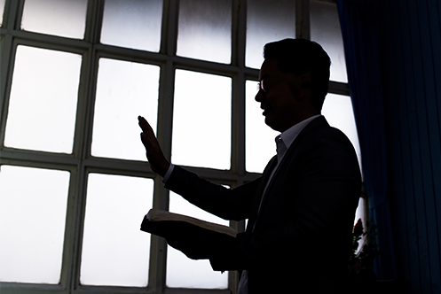 Man holding bible with left hand, right hand raised, wearing black suit, in a room