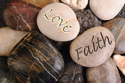 Pile of smooth stones, two stones with the words love and faith