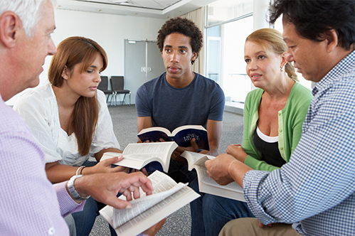five people sitting in a cirlcle on chairs, holding open bibles, discussing