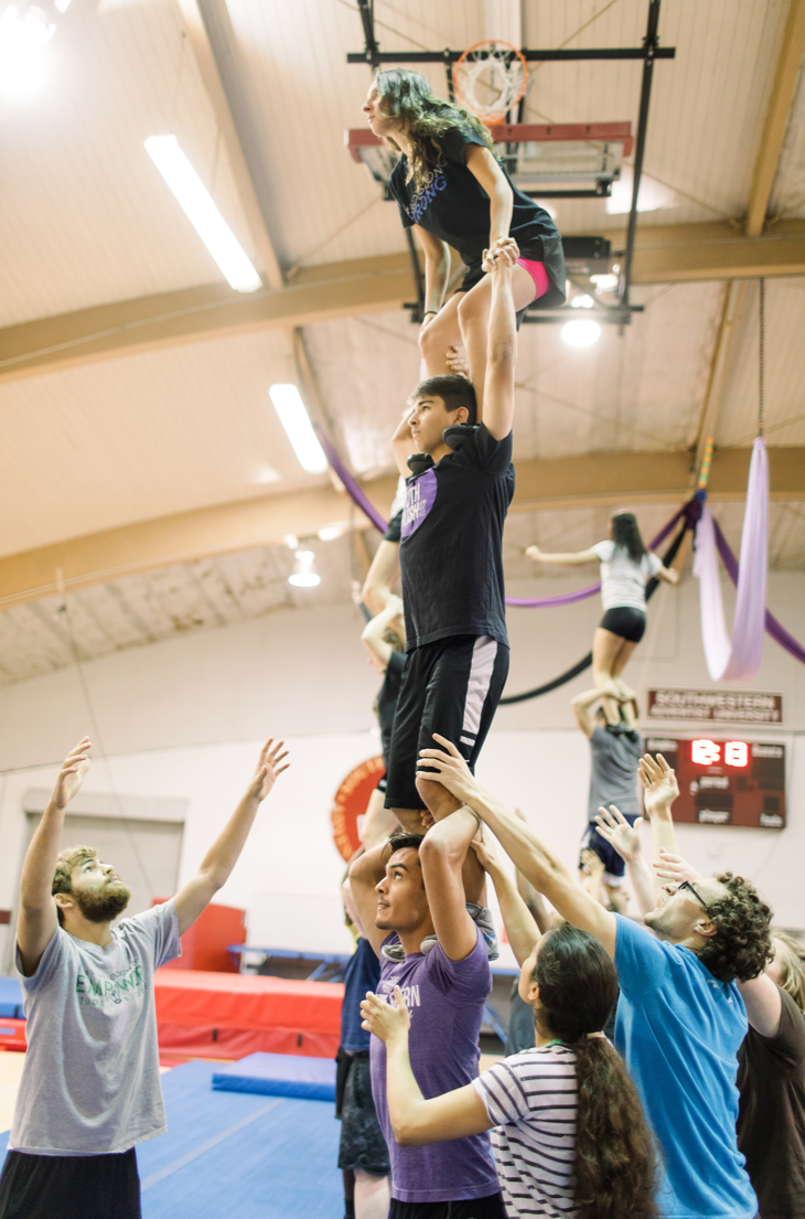 At the gymnasium, three swat members perfrom a trick with each perosn standing on top of each others shoulders