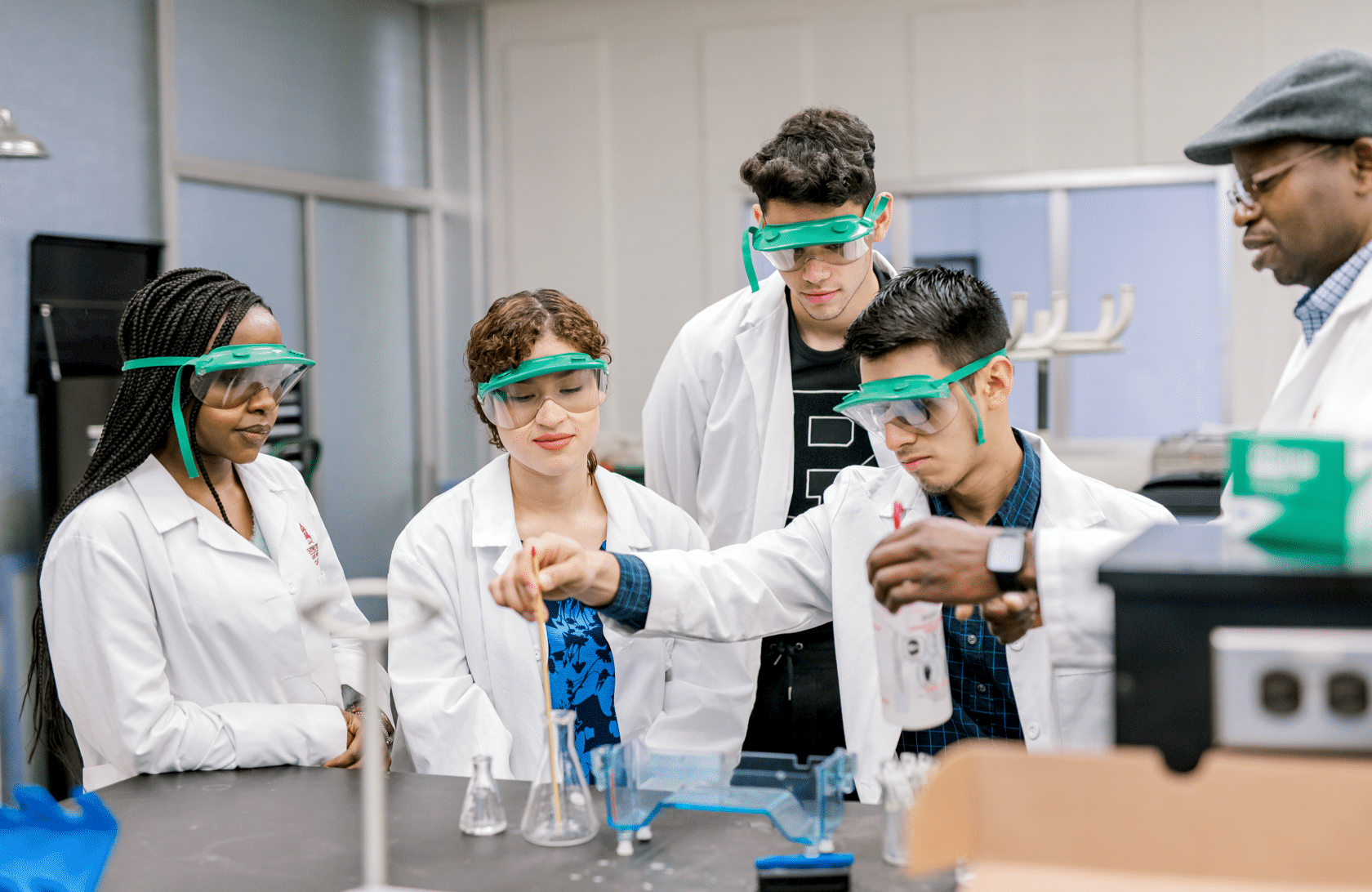 Groups of students with lab coats in lab doing an experiement with the professor