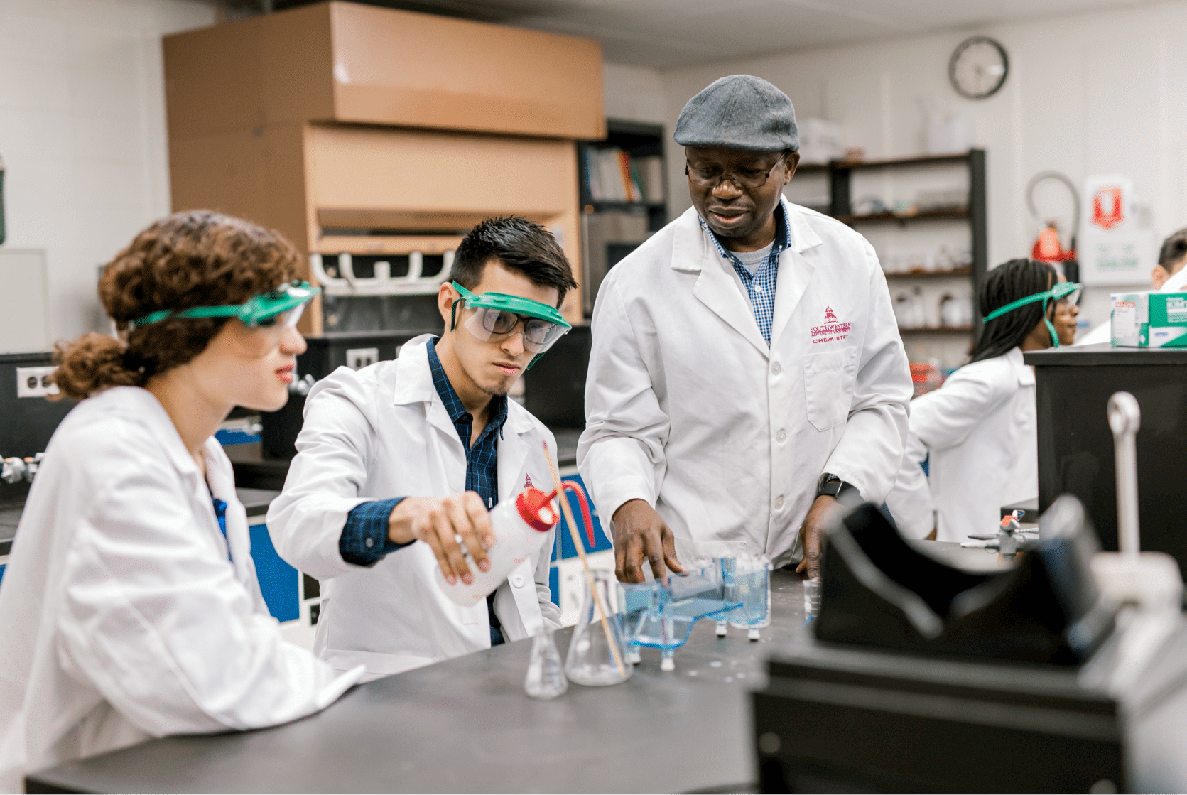Two students, dressed in lab coats and googles, begin to conduct their lab with the help of their professor