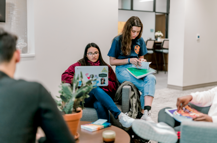 A student sits on a single couch and types on her laptop while her friend sits on the armrest