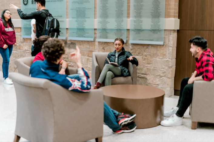 A small group of 4 students sit in single couches talking with each other