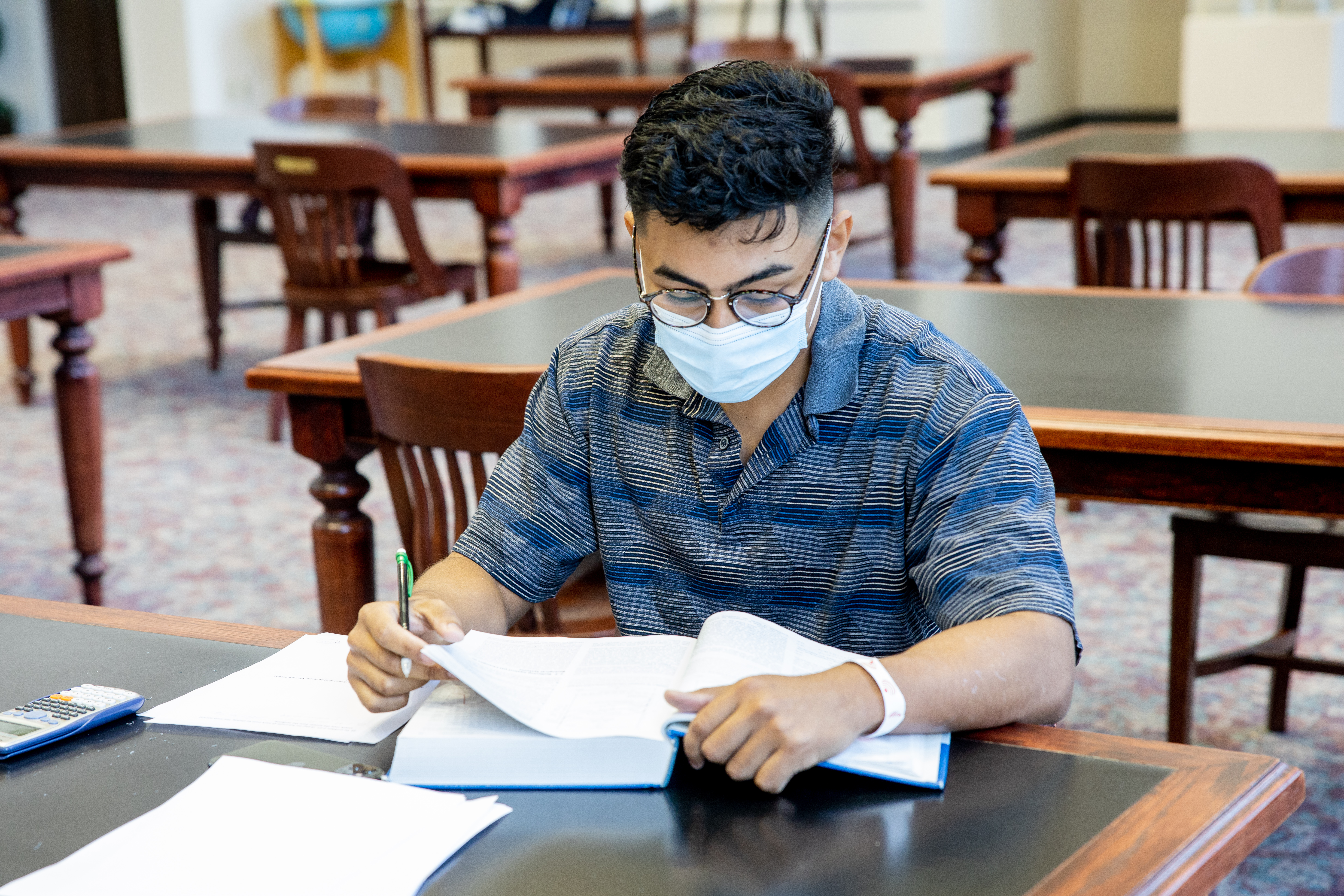 Student wearing a mask sits at a table in the library reading from a textbook.