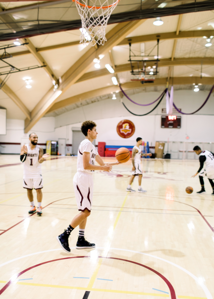 A group of basketball players in uniform practice and throw the ball around at the gymnasium