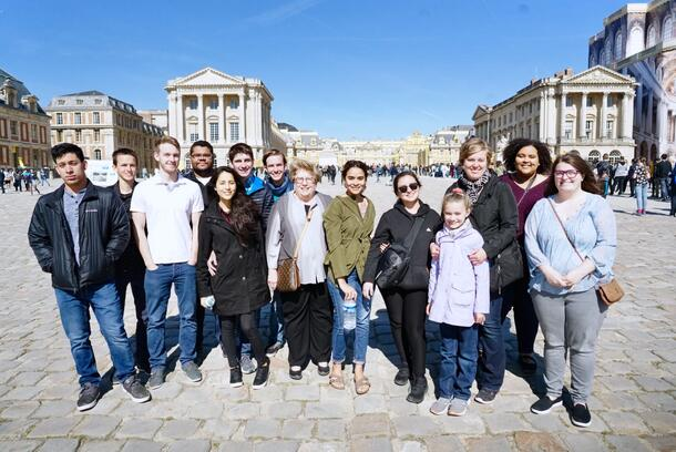 The group of students from the Honors class smile as they group together in front of the Versailles Palace.