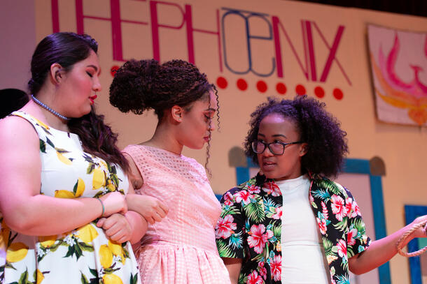 Three women, stand in front of their play background, and look at each other as the speak