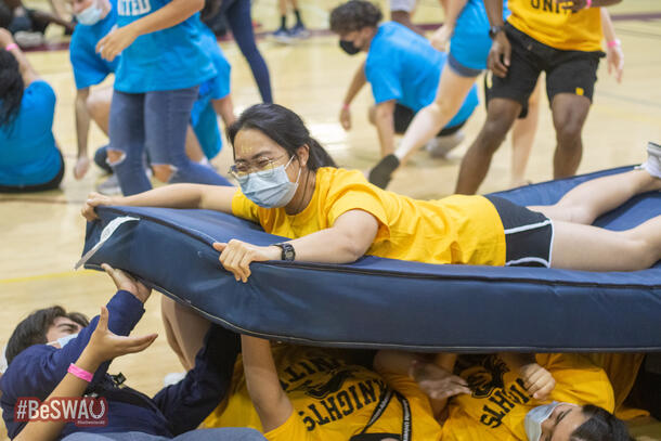 A student, wearing a yellow shirt to match her teammates, smiles as she lays on top of a matress that her teammates her holding and passing along.