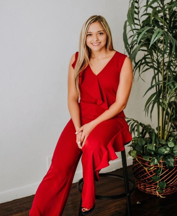 Anabella Lopez poses sitting on a chair next to a plant in a sleeveless red jumpsuit