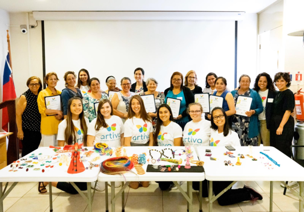 A group photo of women standsing with a certificate in hand, and the Enactus officers smiling while kneeling in front of a table of hand-made goods