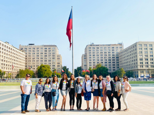 The enactus officers and sponsors stand in front of a large Chile flag and smile