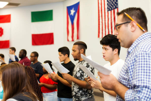 Holding up sheet music, students stand in a semicircle and practice singing