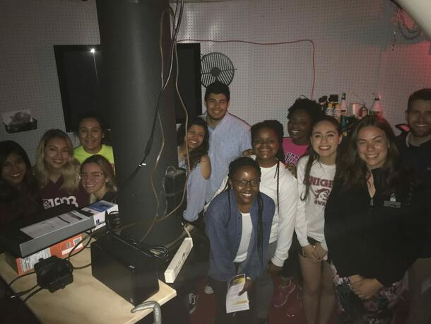 Students smile as they gather around for a picture inside the observatory