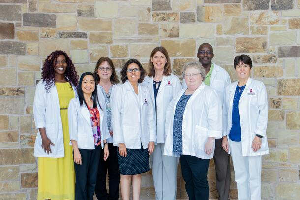 Dressed in their business professional clothes, the nursing administration smiles as they all match in white nursing coats