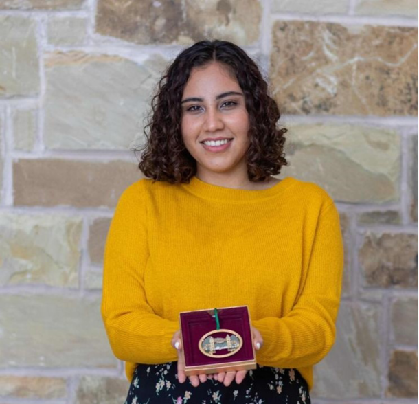 A student with short, curly hair smiles as she carefully holds a golden box with a red lining that holds the Mizpah ornament