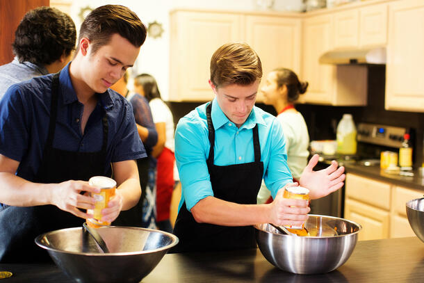 Two students, wearing black aprons, look down as they empty cans of pumpkin puree into a bowl.
