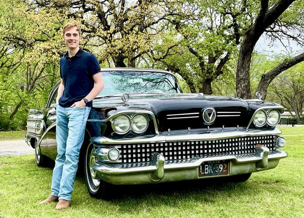 Tony Seery poses leaning against a car in jeans and a polo