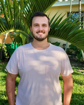 A young man with brown hair smiles as he stand in front of a small palm tree
