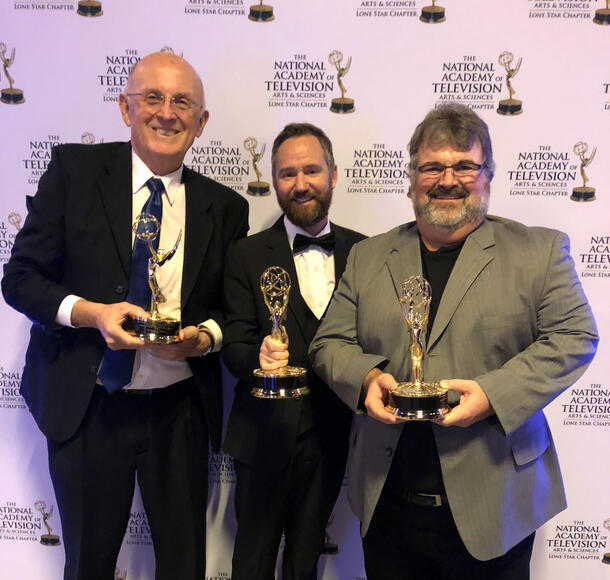 Standing in front of a backdrop, three men, dressed in suits, smile as they hold an award they received from the National Academy of Television.
