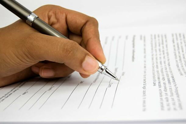 A hand holds a pen that hovers over a document, preparing to sign