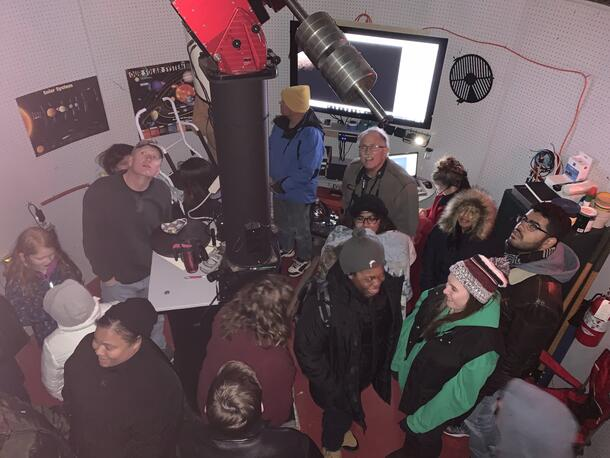 People gather inside the observatory and look up as they view the stars