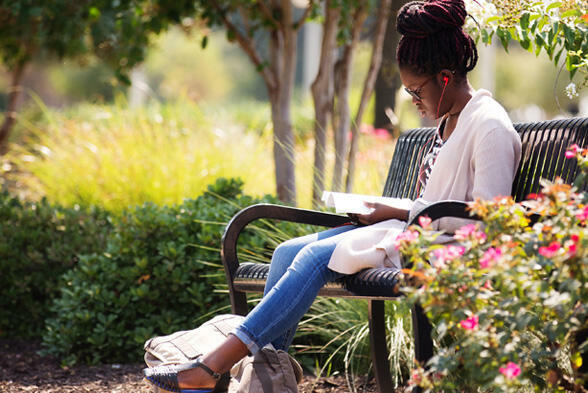 A student sits outside on a bench, reading a book while listening to music through her red headphones