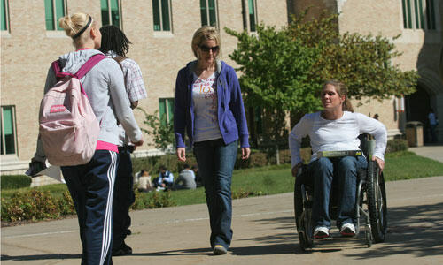 A girl in a wheelchair talks to her friend and they head towards class together