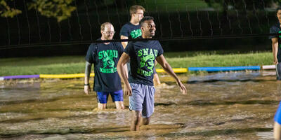 Three students, smile as they stand in muddy water in front of a volleyball net