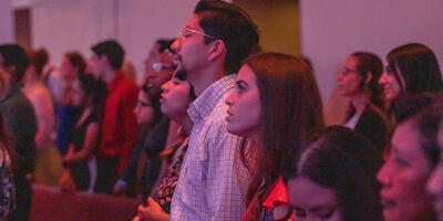 Students, dressed in dresses and button-ups,  gather in the sanctuary stand to sing praise songs
